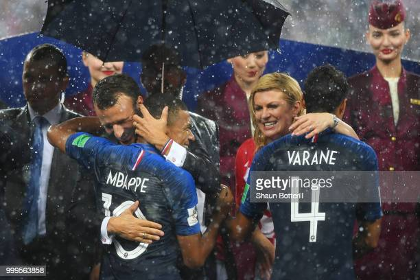 Croatia's President Kolinda GrabarKitarovic and French President Emmanuel Macron congratulate Kylian Mbappe and Raphael Varane of France following...