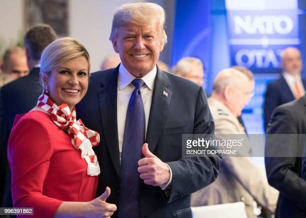 Croatia's President Kolinda GrabarKitarovic and US President Donald Trump give a thumbs up at the start of a working dinner at The Parc du...