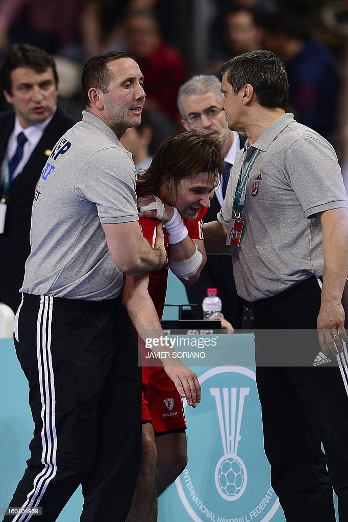 Croatia's right wing Ivan Cupic (C) is helped after being injured during the 23rd Men's Handball World Championships bronze medal match Slovenia vs Croatia at the Palau Sant Jordi in Barcelona on January 26, 2013.