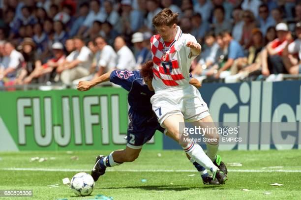 Croatia's Robert Jarni holds off Japan's Akira Narahashi