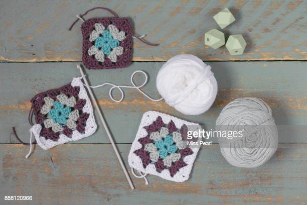 Crochet squares work in progress with crochet hook, beads and yarn