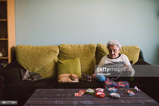 Crocheting senior woman sitting on couch besides her sleeping cats