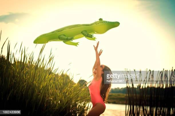 crocodile piscine flotteurs vole au-dessus de la femme à la plage - crocodile photos et images de collection