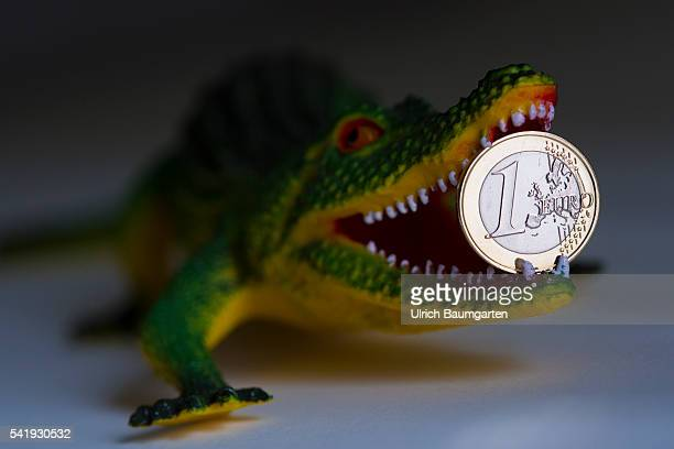 Crocodile with a 1 Euro coin in its mouth Symbol photo on the subjects of proposed referendum on United Kingdom membership of the European Union...
