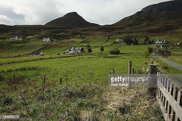 Crofter cottages stand on meadows near Quiraing mountain on October 5 2013 in Staffin Isle of Skye Scotland The Isle of Skye is a popular tourist...