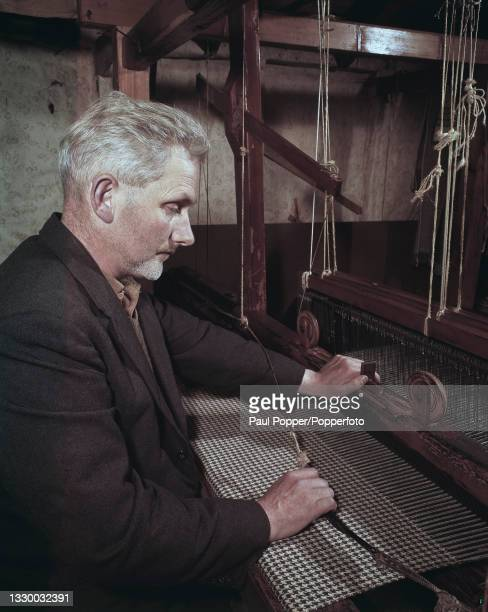 Crofter weaves tweed cloth with a traditional houndstooth pattern on a loom at home in a crofter's cottage near the village of Portnalong on the Isle...