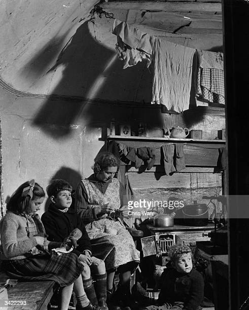 Crofter's family at home in the Outer Hebrides where there is no electricity but there are often fierce winds. Crofters rent their property, which is...