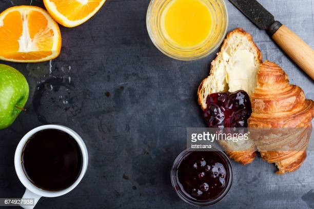 Croissant and coffee, fresh oranges and juice on rustic table. Top view of breakfast table
