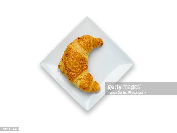 Croissant on a plate viewed from above on white