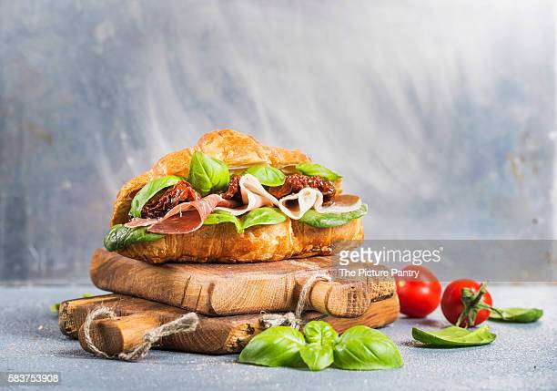 Croissant sandwich with smoked meat Prosciutto di Parma, sun dried tomatoes, fresh spinach and basil on stone textured grey background