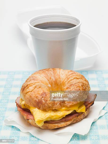 Croissant with scrambled egg, cheese and bacon, cup of coffee