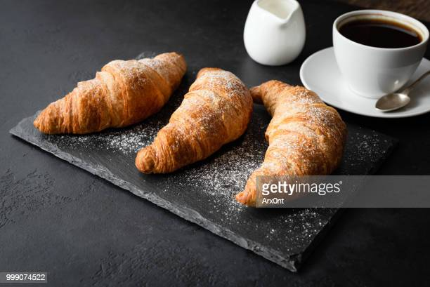 Croissants and coffee on black background