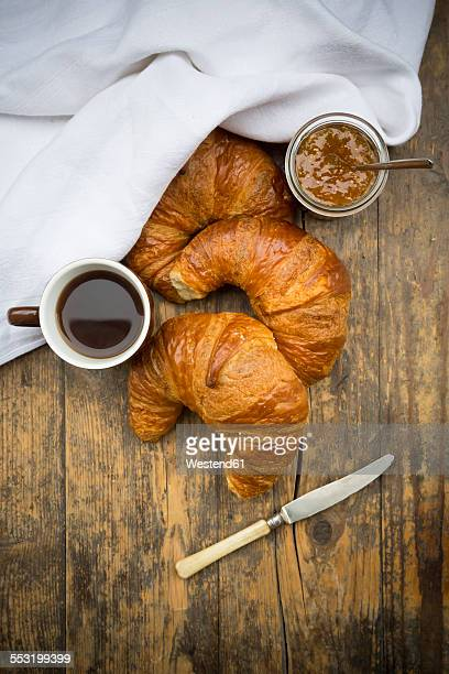 Croissants, fig jam, knife and cup of black coffee