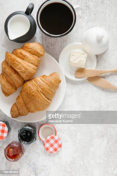 Croissants on plate with coffee and jam