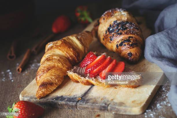 croissants with chocolate cheese spread and fresh strawberries - french food stock pictures, royalty-free photos & images