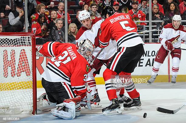 J Crombeen of the Arizona Coyotes and David Rundblad of the Chicago Blackhawks battle for the puck in front of goalie Antti Raanta during the NHL...