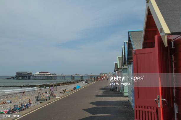 Cromer pier and the sea front seen from the beach huts People enjoy the hot sun on Cromer beach as the weather in England went above 30 degrees for a...