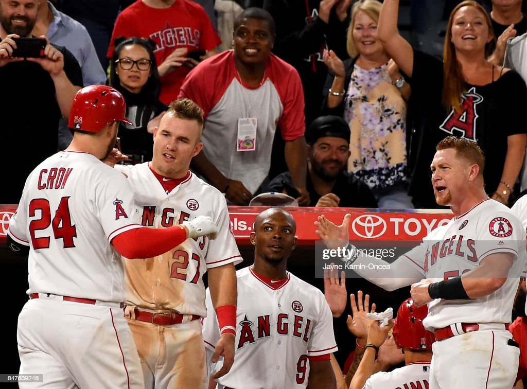 C.J. Cron #24 is greeted at the dugout by Mike Trout #27, Justin Upton #9, and Kole Calhoun #56 of the Los Angeles Angels of Anaheim two run home run in the sixth inning of the game against the Texas Rangers at Angel Stadium of Anaheim on September 15, 2017 in Anaheim, California.