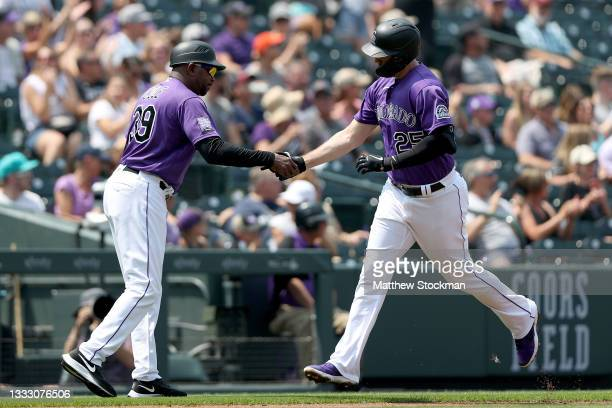 Cron of the Colorado Rockies is congratulated by Stu Cole after hitting a 3 RBI home run against the Miami Marlins in the first inning at Coors Field...