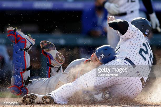 Cron of the Colorado Rockies slides in to score and collides with Austin Barnes of the Los Angeles Dodgers on a wild pitch on Opening Day at Coors...