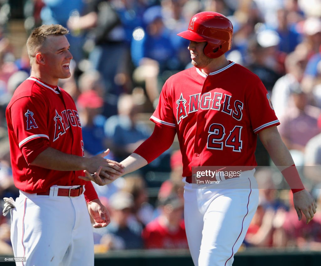 C.J. Cron #24 of the Los Angeles Angels is congratulated by Mike Trout #27 after scoring in the third inning against the Chicago Cubs during the spring training game at Tempe Diablo Stadium on March 6, 2017 in Tempe, Arizona.