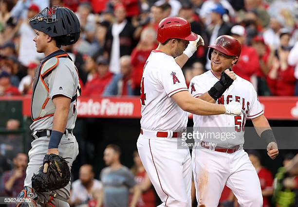 J Cron of the Los Angeles Angels of Anaheim is congratulated by Kole Calhoun after hitting a tworun home run as James McCann of the Detroit Tigers...