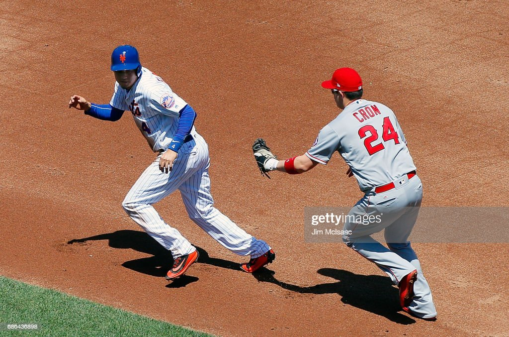 C.J. Cron #24 of the Los Angeles Angels of Anaheim tags out Wilmer Flores #4 of the New York Mets completing a first inning ending double play at Citi Field on May 21, 2017 in the Flushing neighborhood of the Queens borough of New York City.