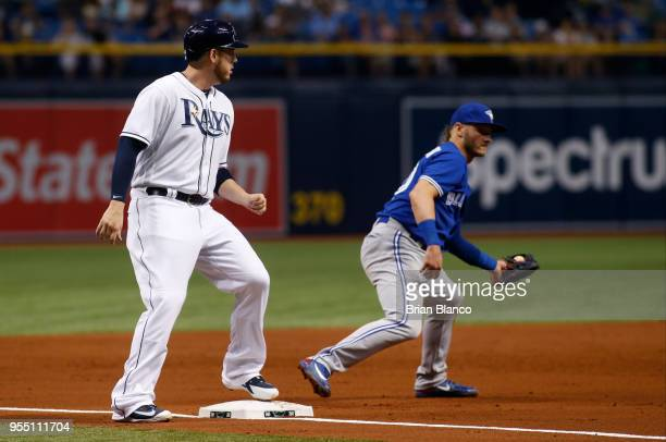 J Cron of the Tampa Bay Rays advances to third base ahead of third baseman Josh Donaldson of the Toronto Blue Jays off of a single by Brad Miller...