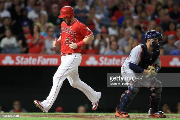 J Cron scores on a single by Brandon Phillips of the Los Angeles Angels of Anaheim as Max Stassi of the Houston Astros looks on during the fourth...