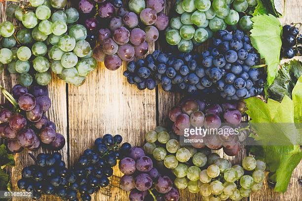Crop and juice, Organic blue and green grapes on wooden table viewed from above, concept wine