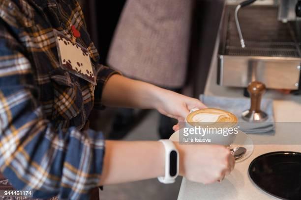 Crop barista serving latte