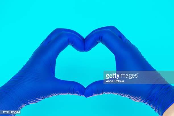crop doctor in gloves gesturing heart - gant de chirurgie photos et images de collection