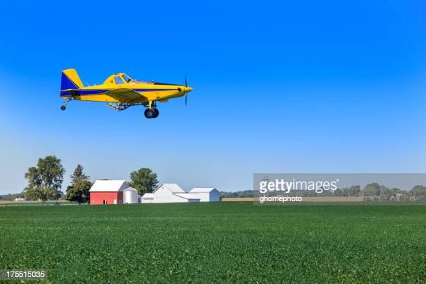 Crop duster flying over farmland