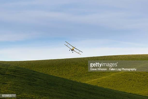 Crop Duster Flying Over Hillside