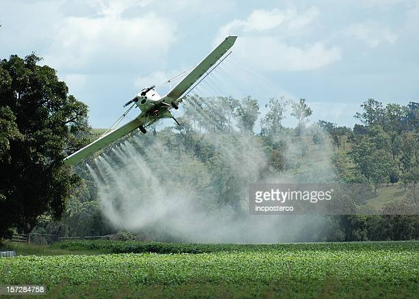 Crop duster plane banking over a field while spraying