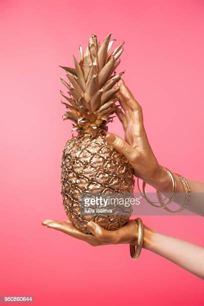 crop hand holding golden pineapple - femininity stock pictures, royalty-free photos & images