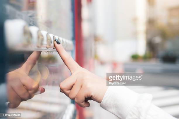 crop image of woman buying a refreshing drink at a vending machine in japan - vending machine stock photos and pictures