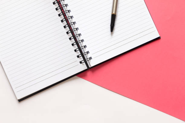 Crop Notepad, notebook and pen on split color pink and white background