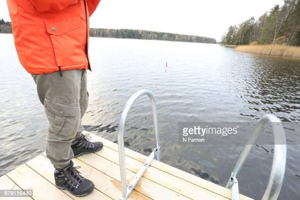 Crop of Man in orange jacket fishing on Jetty