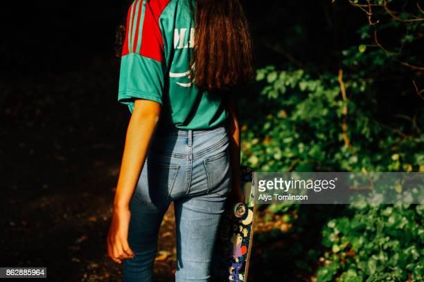 Crop of teenage girl holding skateboard