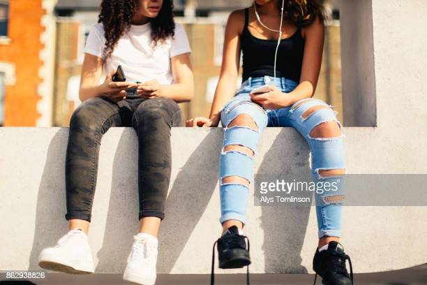 Crop of teenage girls hanging out with smart phones