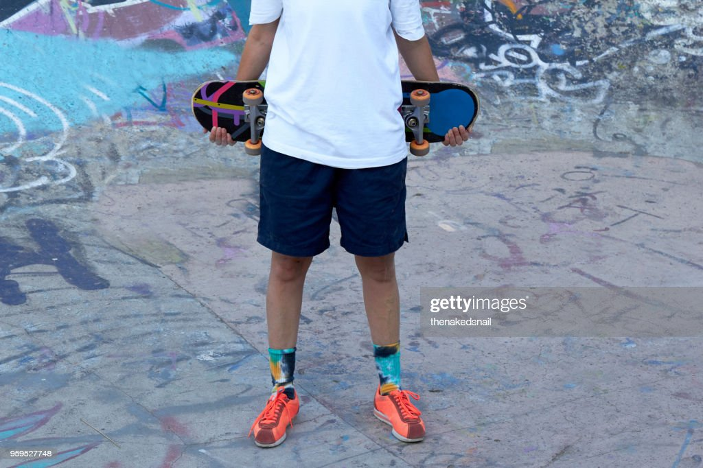 Crop of woman holding skateboard behind back : Stock-Foto