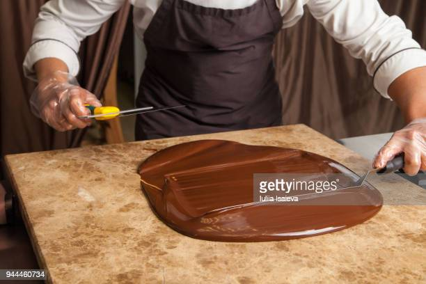 crop pastry man cooling chocolate on marble - chocolat photos et images de collection
