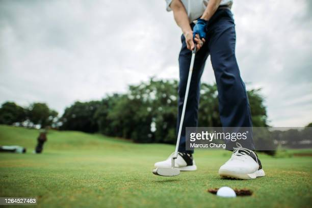crop shot of asian chinese young male golfer tapping the golf ball into a hole at golf course - golfe imagens e fotografias de stock