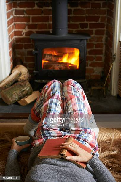 crop shot of woman lying in front of log burner - animal skin rug stock pictures, royalty-free photos & images