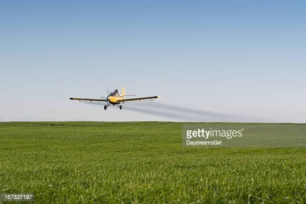 Crop Sprayer Airplane Spraying Green Field with Blue Sky Background