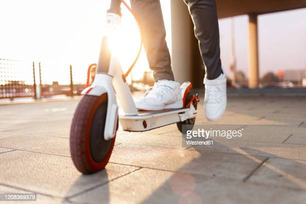 crop view of man riding push scooter at sunset - electric scooter stock pictures, royalty-free photos & images