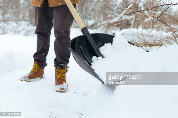 crop view of man shoveling snow - snow shovel stock pictures, royalty-free photos & images