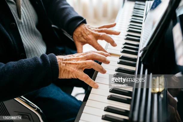 crop view of senior man playing piano - keyboard player stock pictures, royalty-free photos & images