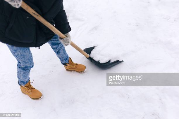crop view of woman clearing walkway with snow shovel - snow boot stock pictures, royalty-free photos & images
